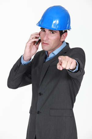 foreman on the phone pointing at something photo