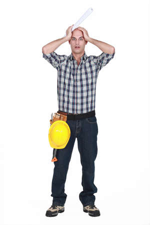 abomination: Construction worker holding his head in horror