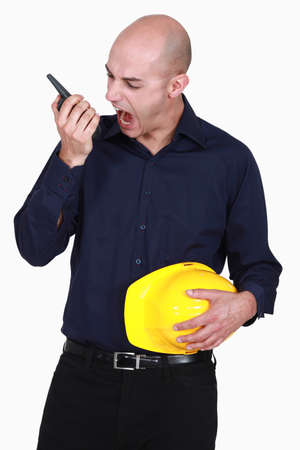 Engineer screaming into a walkie-talkie Stock Photo - 15832806