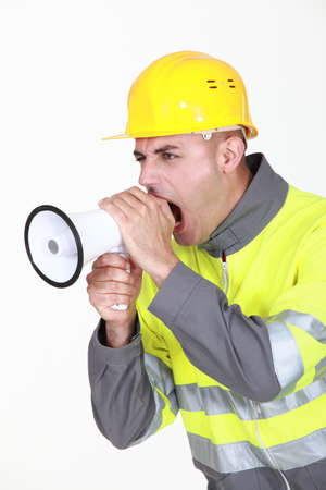 bellowing: Worker with megaphone Stock Photo