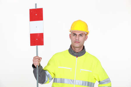 grouch: A traffic guard holding up a sign