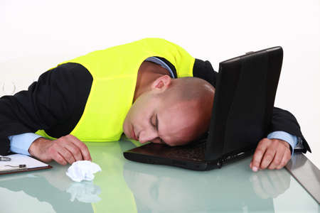 burdened: Exhausted man sleeping on his laptop