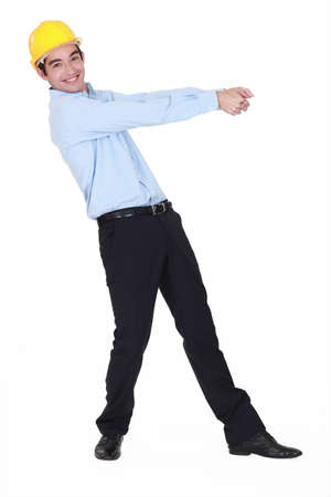 Smiling young engineer pulling an invisible rope Stock Photo