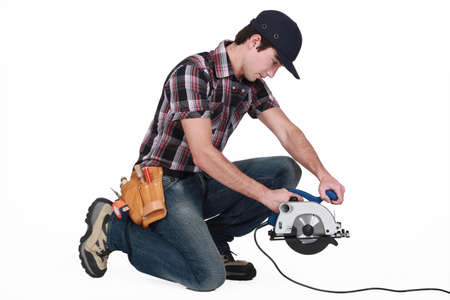 kneeled: Trainee holding a circular saw  Stock Photo