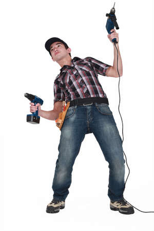 Man fooling about with two power drills Stock Photo