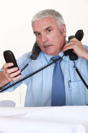 consternation: Overwhelmed man answering ringing telephones