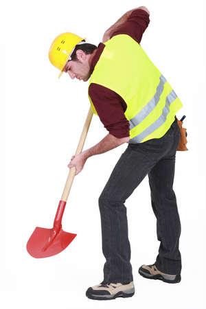 Werknemer graven met een schop Stockfoto