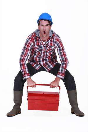 straining: Worker struggling to lift tool box Stock Photo
