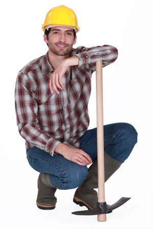 hunker: handsome bricklayer with arm resting on pickaxe
