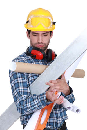 Construction worker overloaded with tools and building materials photo