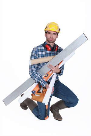 A glowering tradesman carrying building supplies photo