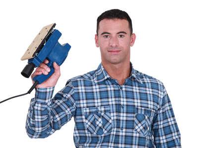 sander: Carpenter holding electric sander