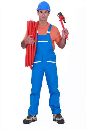 Tradesman holding corrugated tubing and a pipe wrench photo