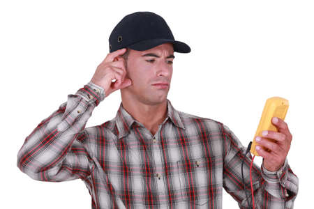 puzzling: Puzzled tradesman staring at his multimeter Stock Photo