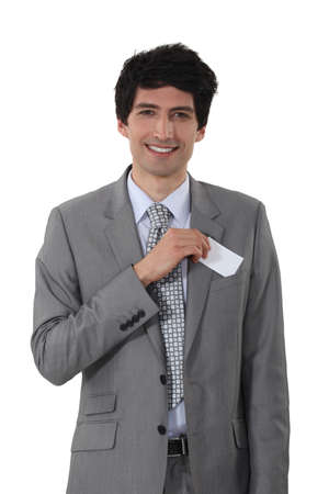 Young businessman removing business-card from pocket photo