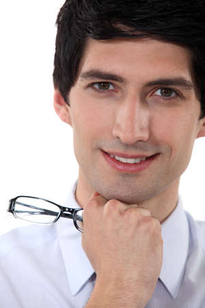 Close-up portrait of a smiling man holding his glasses photo