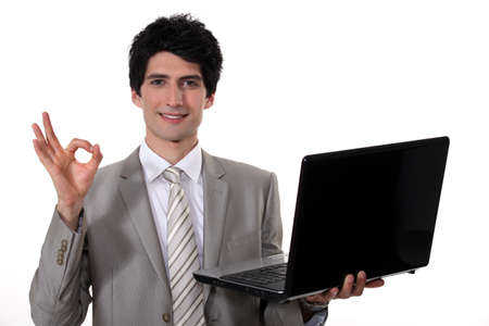 dishy: young handsome businessman with laptop making okay sign