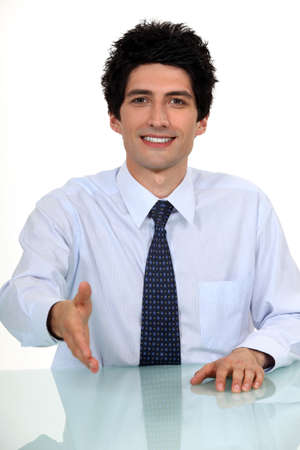 Businessman sat at desk offering to shake-hand Stock Photo - 15859530