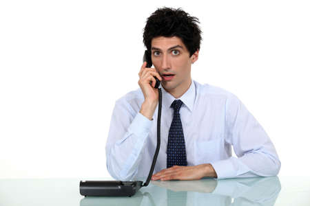 phone calls: Shocked office worker sat with telephone Stock Photo