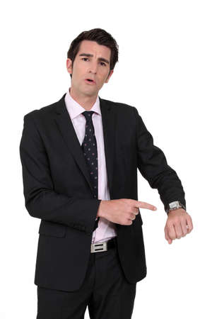 angry businessman: Businessman pointing at his watch