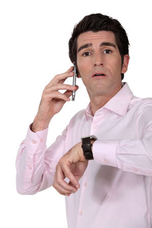 tardiness: Businessman looking at the time Stock Photo