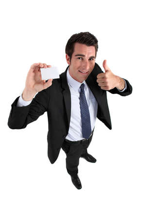 Businessman holding card and making OK gesture Stock Photo - 15852814