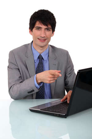 Businessman sat at desk pointing to laptop photo