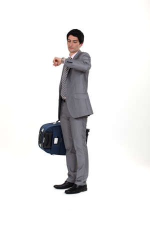 Businessman with suitcase looking at wrist watch photo