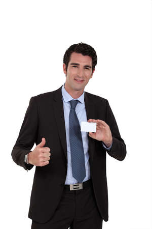Young businessman with business card giving the thumbs-up photo