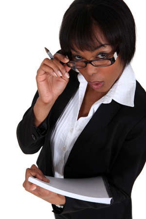 quotas: portrait of black businesswoman looking upwards holding pen and notepad