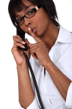 woman on the phone making a sign for silence Stock Photo - 15859527