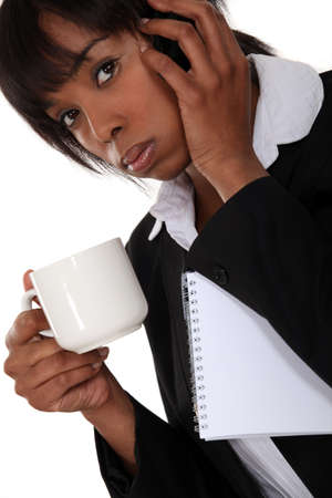 An African American businesswoman on the phone drinking a coffee  photo