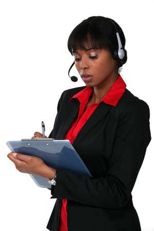 hands free phone: La mujer llevaba un auricular y la escritura en un portapapeles