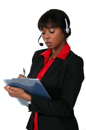 Woman wearing a headset and writing on a clipboard photo