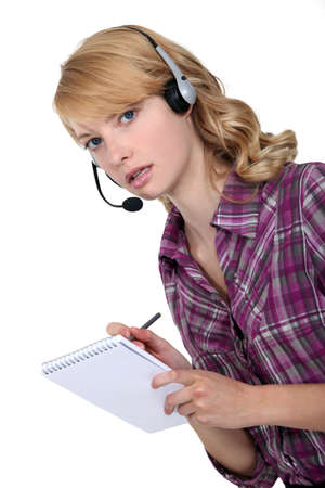 A businesswoman with a headset on taking notes  photo