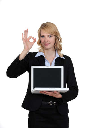 Businesswoman with laptop giving the OK signal photo