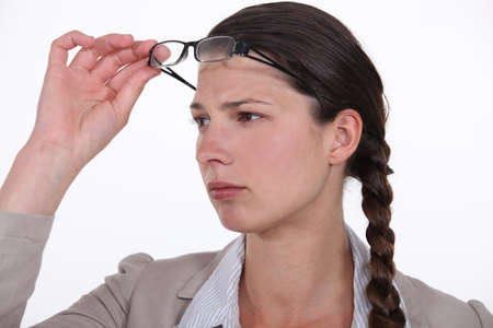 bewilder: Perplexed woman taking her glasses off to get a better look at something Stock Photo