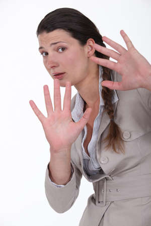 aggravated: woman looking scared with hands stretched forward Stock Photo