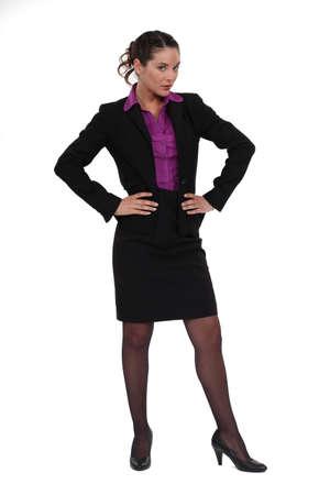 팬티 스타킹: 그녀의 손으로 그녀의 엉덩이에 서있는 사업가 스톡 사진