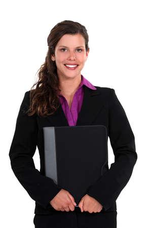 all smiles: pretty businesswoman all smiles holding laptop