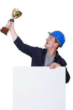 Tradesman holding up a trophy photo