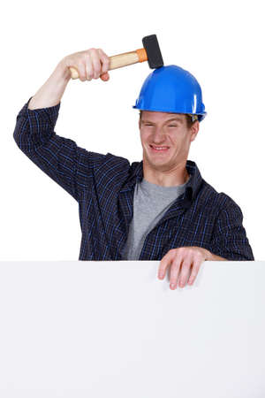 laborer hitting his head with hammer photo