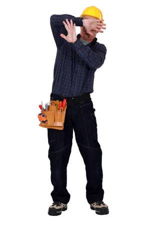 hombre cayendose: artesano proteger su cara Foto de archivo