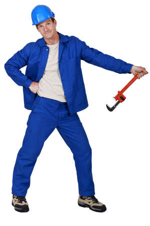 kooky: Goofy tradesman holding a pipe wrench Stock Photo