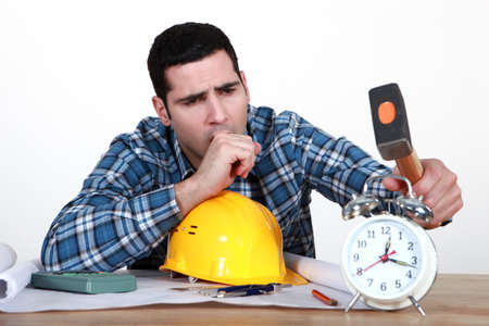 Tired tradesman about to smash his alarm clock photo