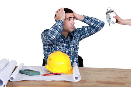 anguished: lavoratore stressato guardando un orologio Archivio Fotografico