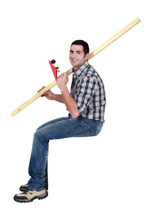 smoothen: Man holding a wooden plank and a plane while sitting on a block