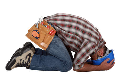 tribulation: Tradesman with his head in his hands Stock Photo
