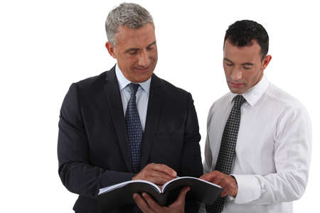 solicitor: Two businessmen reading document Stock Photo