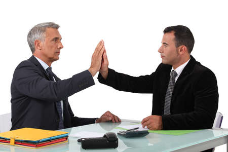 Two business men high-five photo